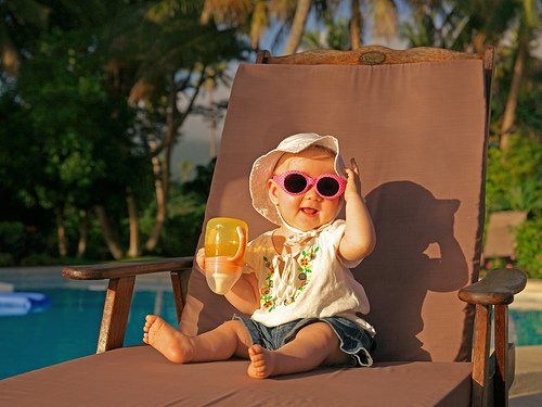Baby sitting on a chair on holiday in the sun